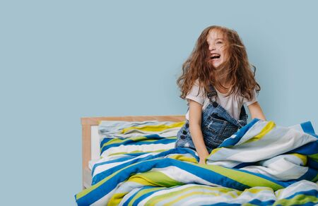 Little girl in jeans overalls is playing actively, frolicing in her bed with striped colored sheets over blue background.