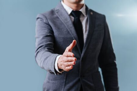 Businessman in a gray suit is extending his right hand to do a handshake over blue background. Cropped, no head.