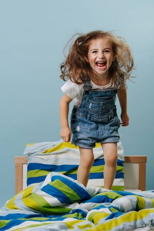 Laughing little girl in jeans overalls is playing actively, jumping in her bed with striped colored sheets over blue background.