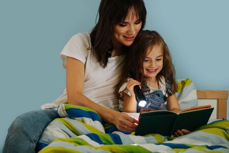 Happy mother and her little daughter are absorbedly reading illustrated book in girls bed before going to sleep. They are using flashlight, for better experience, to create atmosphere.