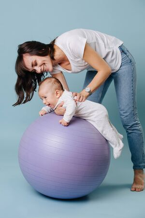 Happy mother carefully and gently doing exercises with her infant child baby on purple yoga ball over blue background. She rolling baby on a ball. Baby is excited and having fun. Side view.