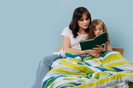 Mother and her little daughter are absorbedly reading illustrated book under the bright lights, in girls bed before going to sleep. Over blue background. Zdjęcie Seryjne