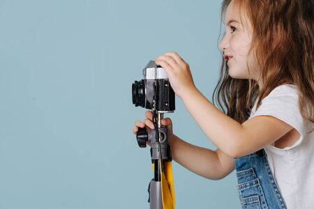 Little preschooler girl with brown wavy hair is taking an image with a vintage mirrored camera, fixed on a tripod. Over blue background. Side view.