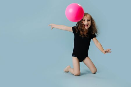 Little girl in a black leotard with pink gymnastic ball over blue background. She is doing element with a ball. 免版税图像