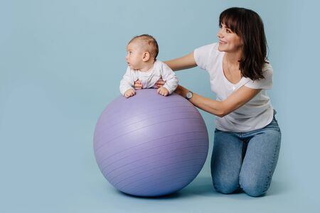 Happy mother carefully and gently doing exercises with her infant child baby on purple yoga ball over blue background. Baby is lying on stomach, holding head steady. They both are looking away.
