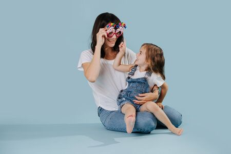 Mother and daughter playing with happy birthday glasses over blue background 版權商用圖片
