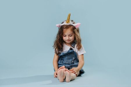 Little girl, wearing unicorn headband, sitting on the floor over blue background