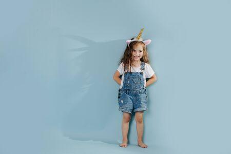 Little girl, wearing unicorn headband, leaning against blue wall.