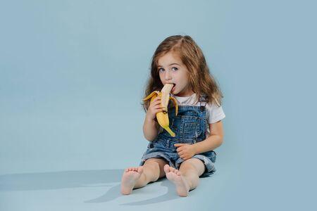 Klein meisje eet banaan, zittend op de vloer op een blauwe achtergrond Stockfoto