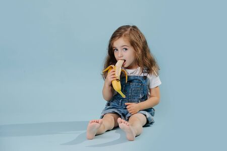 Little girl is eating banana, while sitting on the floor over blue background