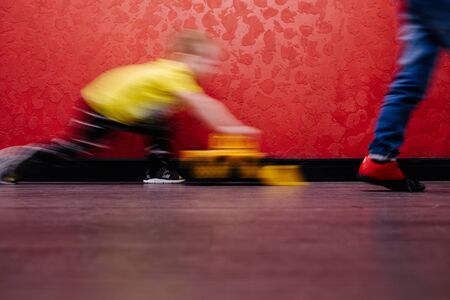 Little boy in yellow shirt and sneakers is playing with plastic model bulldozer in a public place next to strangers. He is motion blurred from running. Over red wallpapers Zdjęcie Seryjne