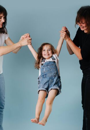 Two women swinging toddler girl in denim overall holding her hands isolated on blue background