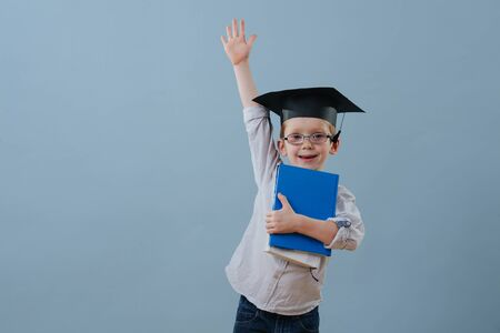 Cute smiling little ginger boy in glasses, wearing student hat holds stack of books in hands over blue background. Half length. He's eagerly raising his arm in a fashion to answer teachers question. Stock fotó
