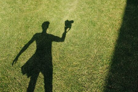 The shadow of the photographer with camera on the freshly mowed green lawn at mid summer sunny day. He has a bag on his side, his left hand slightly extended. Banque d'images - 132561662