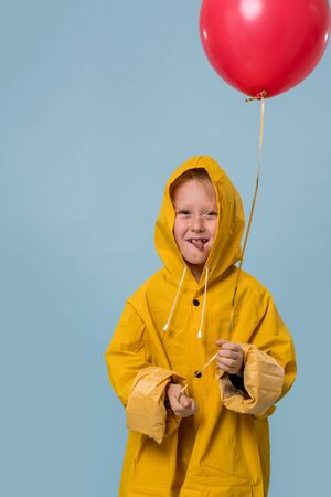 Little boy in yellow raincoat with red balloon over blue background. Horror movie style for halloween. With grimace and tongue out. Half length.