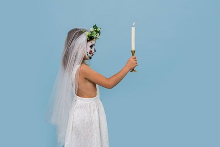 Little girl in bridal gown holding candlestick with lit candle. She wears veil and hair wreath, painted scary halloween skull mask over blue background. Side view.