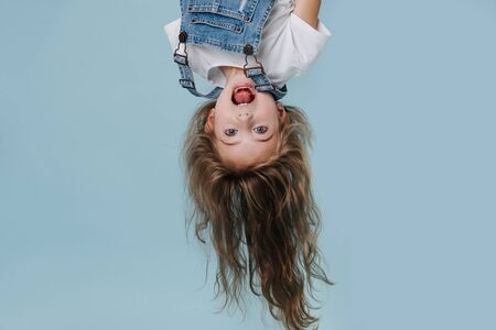 beautiful little girl hanging upside down and screaming cheerfully on blue background