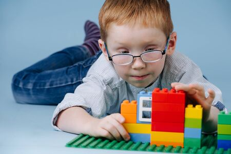 Little ginger boy is lying on the floor, assembling small house piece by piece from tipped plastic blocks of construction toy. He's fully immersed in a process. Over blue background. Reklamní fotografie