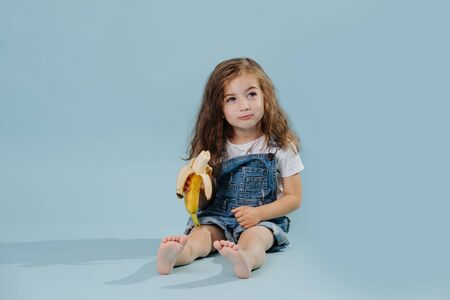 Toddler girl with a sly look sitting on blue background and eating banana