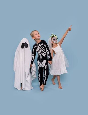 Three adorable little kids in Halloween costumes over blue background. Ghost, skeleton and dead bride are holding hands. They look up, pointing at something.