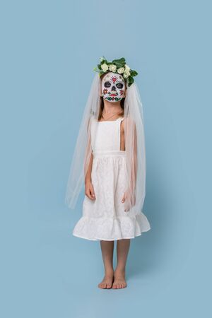 Little girl in bridal gown, veil and hair wreath wears painted scary halloween skull mask over blue background. She stands still and unalive, looks at camera. low angle. 스톡 콘텐츠