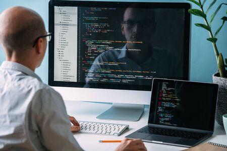 Łysy kaukaski programista w okularach siedzi za biurkiem, przed dwoma czarnymi ekranami, laptopem i monitorem, przyglądając się uważnie, analizując linie kodu. Jest bardzo uważny i skupiony. Zdjęcie Seryjne
