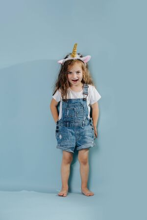 verspieltes Kleinkindmädchen, das auf blauem Hintergrund steht und Stirnband mit Einhornhorn und Ohren trägt Standard-Bild