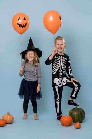 Two cute happy kid siblings wearing witch and skeleton costumes holding scary orange halloween balloons with faces over blue. Pumpkins laid around them.