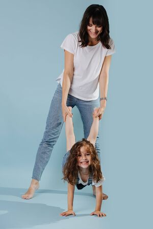 happy mom and daughter play active games, daughter walks on hands isolated on blue background Reklamní fotografie