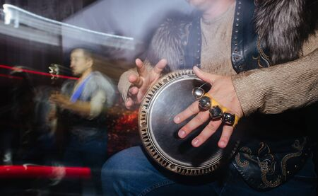 Close up of musician in extravagant native clothes, furry jacket and jeans, playing on hand drum during concert. Motion blurred surroundings with long lines from colored lamps. Cropped. No head.