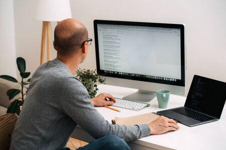 Kale blanke programmeur met bril zit achter het bureau, voor twee schermen, laptop en monitor, één zwarte, volledige coderegels, andere wit met google-zoekopdracht. Stockfoto