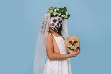 Little girl in bridal gown, veil and hair wreath wears painted scary halloween mask holding cracked skull prop in her hands over blue background. Side view. Stock Photo