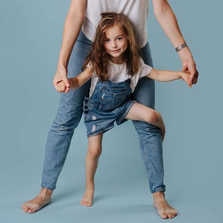 Beautiful model looking girl with curly hair dressed in denim overall a playing with mom's legs Zdjęcie Seryjne