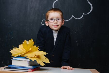 Little ginger boy in glasses and uniform is participating in a traditional first day of school portrait photo session. He's standing behind the desk over blackboard. Books and yellow maple leafs.