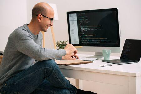 Łysy kaukaski programista w okularach siedzi za biurkiem, przed dwoma czarnymi ekranami, laptopem i monitorem, analizując linie kodu. Śmieje się z czegoś radośnie. Zdjęcie Seryjne