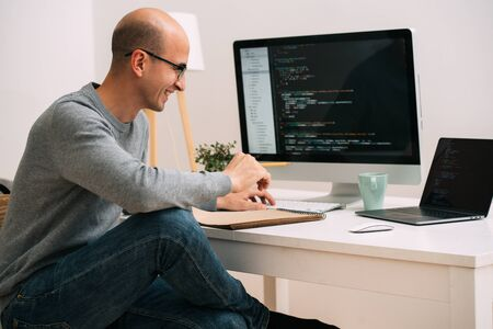 Un programmeur caucasien chauve à lunettes est assis derrière le bureau, devant deux écrans noirs, un ordinateur portable et un moniteur, analysant les lignes de code. Il rit joyeusement de quelque chose. Banque d'images