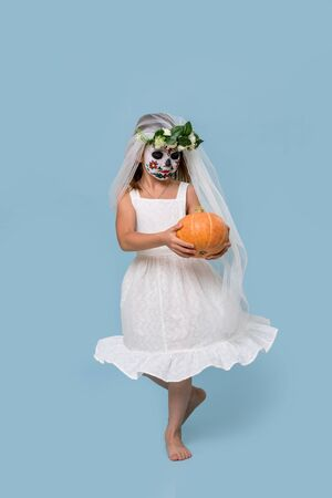 Little girl in bridal gown, veil and hair wreath wears painted scary halloween skull mask over blue background. She's holding pumpkin, doing curtsy with her eyes closed. low angle.