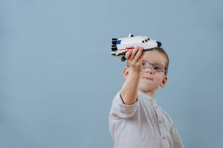 Little ginger boy in glasses plays with space shuttle lego model over blue background. He's absorbed in a process. He's imagining it flies past him. Half length. Stock Photo