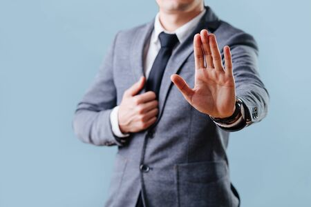 Businessman in a gray suit is making stop gesture by extending hand with the palm outward, holding lapel with his second hand over blue background. Cropped, no head. Stock Photo