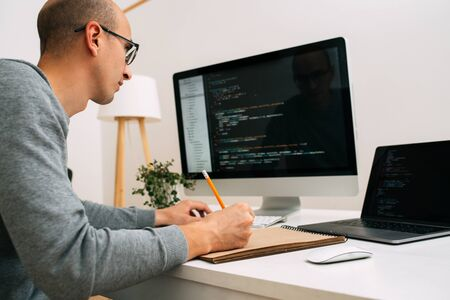 Kale blanke programmeur met een bril zit achter het bureau, voor twee zwarte schermen, laptop en monitor, en analyseert coderegels. Hij maakt met potlood aantekeningen in zijn papieren notitieboekje.