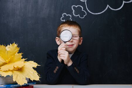 Little ginger boy in uniform is participating in a traditional first day of school portrait photo session. He sits behind the desk over blackboard. He's looking through the magnifying glass.
