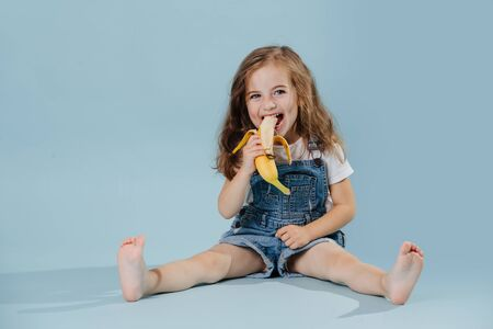Adorable happy barefoot little preschooler girl with brown wavy hair is eating banana, sitting on the floor with legs spread. She wears jeans overalls and white shirt. over blue background