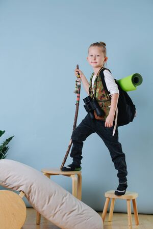 Portrait of a handsome little boy playing hiker at home, standing on stools with different height. He is holding curved hiking stick, decorated with colored threads. He is dressed like a traveler. Banque d'images
