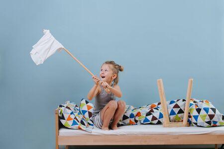 Un petit garçon est assis sur un lit défait, agitant un drapeau blanc sur des murs bleus. Il imagine que le lit est sa forteresse, il la défend. A côté de lui se trouve un tabouret placé à l'envers, censé être une tour.