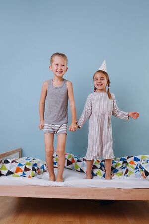 Boy and girl holding hands, jumping on the bed together