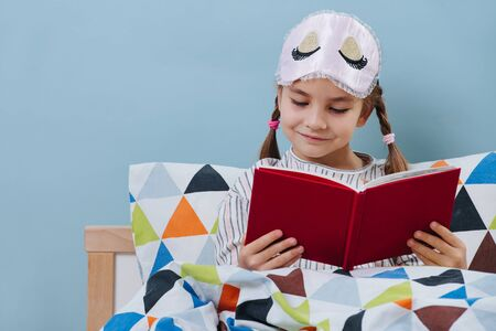 Diligent little girl reading in bed in pajamas before going to sleep over blue
