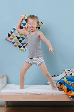 little boy standing on bed, ready for a pillow fight over blue walls