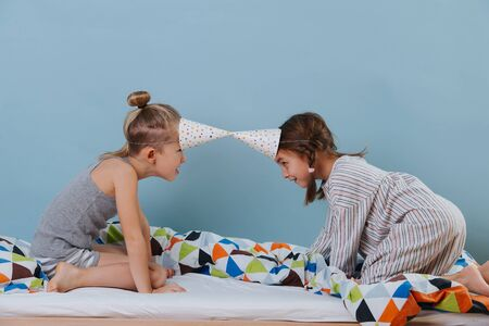 Boy and girl butting heads, playing in the bedroom with party cone hats
