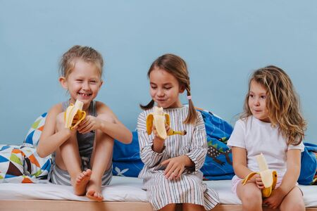 Three kids in sleeping clothes sitting on unmade bed, eating bananas