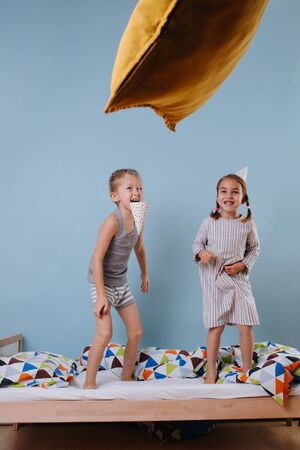 Boy and girl with party cone hats jumping on the bed together Фото со стока